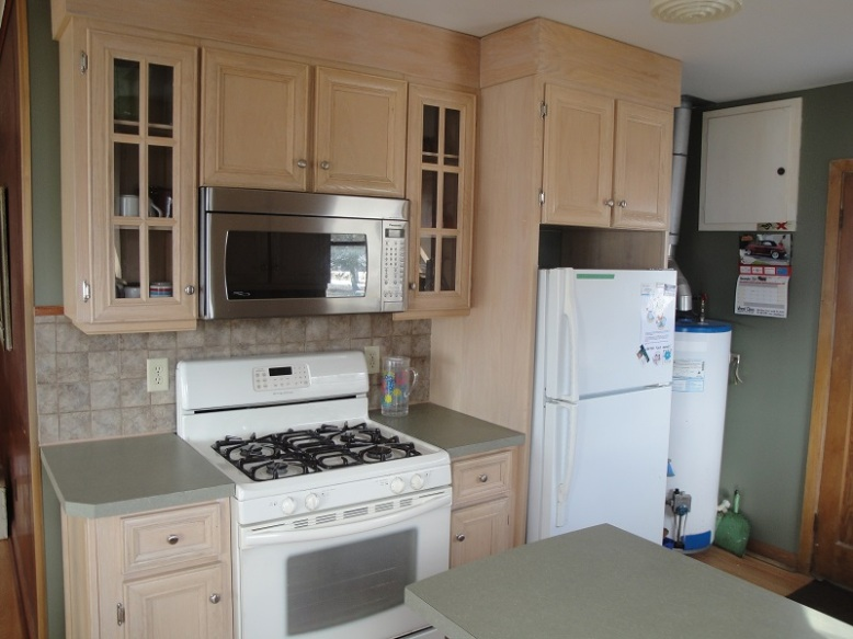 Newly renovated kitchen includes microwave, fridge and freezer, gas stove and oven, dishes, pots, pans, cutlery and more.